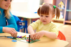 Teacher and little girl play with plasticine Royalty Free Stock Images