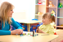 Teacher and little girl play with plasticine Stock Image
