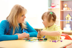 Teacher and little girl play with plasticine Stock Photography