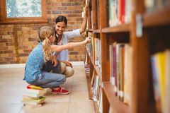 Teacher and little girl selecting book in library Stock Image