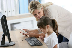 Teacher and little girl using computer and tablet Royalty Free Stock Images