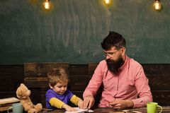Teacher and little kid sitting at desk with books and teddy bear. Schoolboy playing with copybook. Strict teacher in stock image