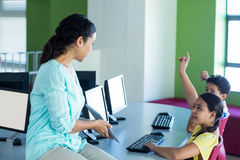 Teacher looking at children raising hands. Female teacher looking at children raising hands while holding digital tablet in computer class Royalty Free Stock Photo