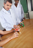 Teacher Looking At Molecular Structure At Desk. Mature male teacher looking at molecular structure at desk with female colleague in background Royalty Free Stock Photo