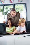 Teacher Looking At Schoolchildren Using Desktop Pc. Mature male teacher looking at schoolchildren using desktop PC in computer lab Royalty Free Stock Images