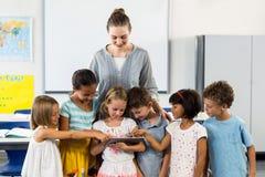 Teacher looking at schoolchildren using digital tablet. Female teacher looking at schoolchildren using digital tablet in classroom Stock Photo