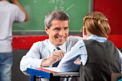 Teacher Looking At Schoolgirl Sitting At Desk. Happy mature teacher looking at schoolgirl sitting at desk in classroom Stock Photos