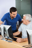 Teacher Looking At Senior Man Using Computer Classroom. Happy male teacher looking at senior men using computer at classroom Royalty Free Stock Photos