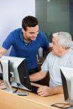 Teacher Looking At Senior Man Using Computer Classroom Royalty Free Stock Photos