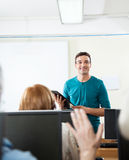 Teacher Looking At Student Raising Hand During Computer Class. Happy male teacher looking at female student raising hand during computer class Stock Images