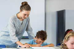 Teacher looking at student writing on book. Female teacher looking at student writing on book in classroom Stock Photo