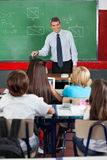 Teacher Looking At Students In Classroom. Happy male mature teacher looking at students in classroom Royalty Free Stock Images