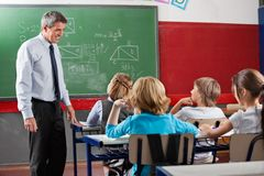 Teacher Looking At Students Sitting In Classroom. Side view of mature male teacher looking at students sitting in classroom Royalty Free Stock Photo