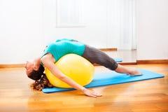 Teacher making body exercises on a yellow ball Royalty Free Stock Photo