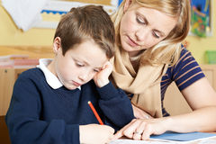 Teacher With Male Elementary School Pupil With Problem. Teacher Helping Male Elementary School Pupil With Problem Royalty Free Stock Photos