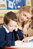 Teacher With Male Elementary School Pupil With Problem Royalty Free Stock Images