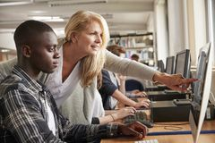 Teacher With Male Student Working On Computer In College Library Royalty Free Stock Photography