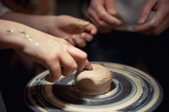 Teacher man teaches a child how to make a ceramic plate on the potters pile. Royalty Free Stock Photography