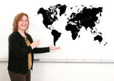 Teacher and map. A middle aged woman teacher showing a black map on the whiteboard Royalty Free Stock Photos