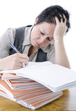 Teacher marking students work. Bored / frustrated teacher marking students work at desk royalty free stock photography