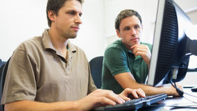 Teacher and mature student in computer room Stock Images