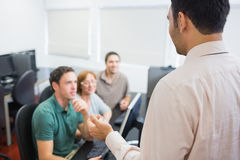 Teacher and mature students in computer room Stock Photos