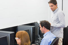Teacher and mature students in computer room Stock Photo