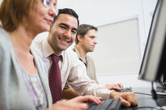 Teacher and mature students in computer room Royalty Free Stock Photos