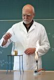 Teacher mixes chemicals in a laboratory stock images