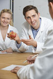 Teacher With Model Of Heart In Biology Class stock images