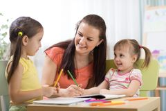 Teacher mom working with creative kids. Teacher or mom working with creative kids in kindergarten or home Stock Photography