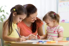 Teacher mom working with creative kids stock photo