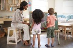Teacher At Montessori School Helping Children in Art Class Stock Photos