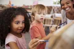 Teacher At Montessori School Helping Children in Art Class Royalty Free Stock Photos
