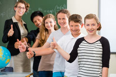 Teacher motivating students in school class stock images