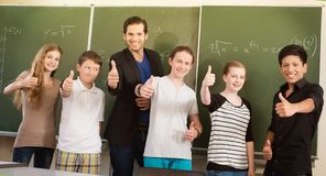 Teacher motivating students in school class stock photo