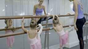 Teacher near ballet shows young children dance position. Two girls learn to do exercises on wooden crossbeam, which is taught by woman in dance studio stock video