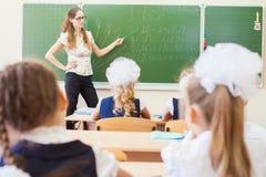 Teacher near blackboard teaching children math or geometry, holding pointer. Stock Images