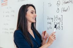 Teacher near whiteboard explains the rules. Learn foreign language. royalty free stock photo