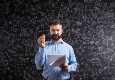 Teacher with notebook against big blackboard with symbols and fo Royalty Free Stock Photography