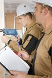 Teacher observing apprentice in drilling wall. Teacher observing the apprentice in drilling the wall stock image