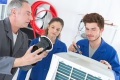 Teacher observing students working on electrical appliance royalty free stock image