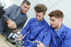 Teacher observing students working on electrical circuits royalty free stock image