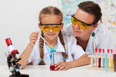Teacher overseeing chemical experiment in science class Stock Image