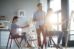 Teacher by painting student stock photography