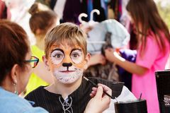 Teacher paints face of young actor. To resemble a tiger as he prepares for  production Royalty Free Stock Image