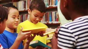 Teacher passing out books in library stock footage