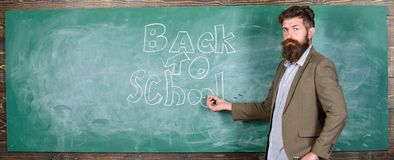 Teacher passionate job ability reach out students. Man bearded teacher missed his work during vacation. Back to school. Concept. Teacher near chalkboard holds stock images