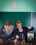 The teacher of physics explains to the pupil interaction of a magnetic field and electric field Stock Photo