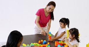 Teacher play build blocks toy with students. Close up scene video of Asian teacher play colorful build blocks toy with Asian students together, concept for stock video